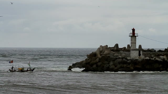 lighthouse on beachfront surrounded by rocks/ abidjan/ ivory coast - côte d'ivoire stock videos & royalty-free footage