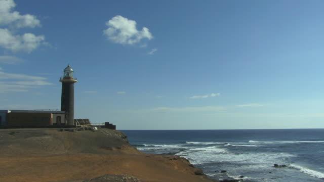 ws lighthouse on rocky coast above ocean/ puerto de la cruz, tenerife, canary islands - okänt kön bildbanksvideor och videomaterial från bakom kulisserna