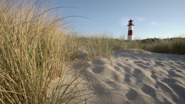 stockvideo's en b-roll-footage met lighthouse on the dunes (sunset) - helm apparatuur