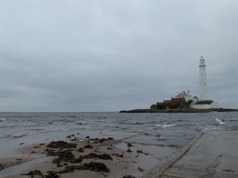 stockvideo's en b-roll-footage met lighthouse, sea lapping shore, calm, overcast - whitley bay