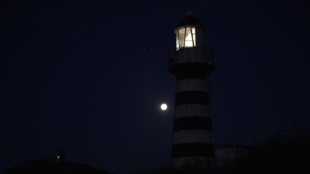 lighthouse shines at night on shore of pacific ocean - lighthouse stock videos & royalty-free footage