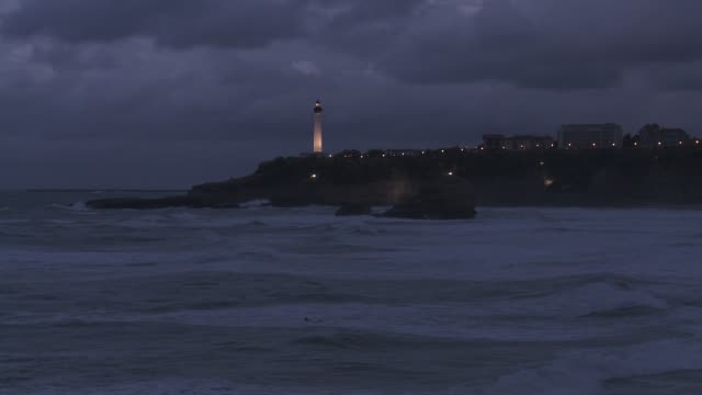 A lighthouse shines on the edge of a peninsula as waves roll into shore.