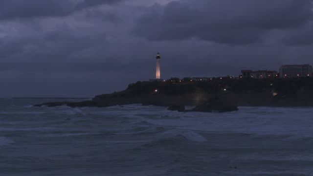 a lighthouse shines on the edge of a peninsula as waves roll into shore. - lighthouse stock videos & royalty-free footage