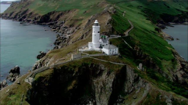 A lighthouse stands on the rugged coastline of southwest England. Available in HD.