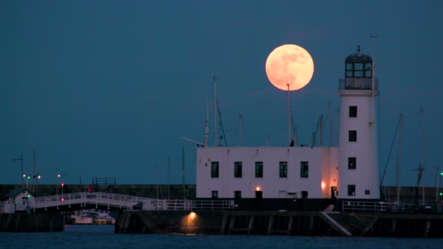 lighthouse & supermoon rise, scarborough, north yorkshire, england - supermoon stock videos & royalty-free footage