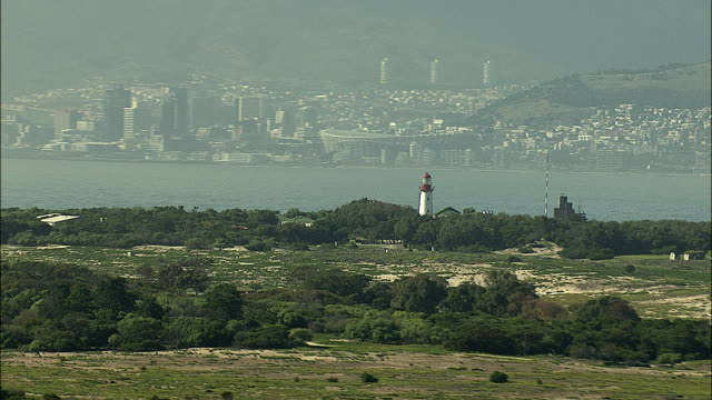 AERIAL WS ZO Lighthouse with cityscape and Table Mountain in background, Robben Island, Western Cape, South Africa