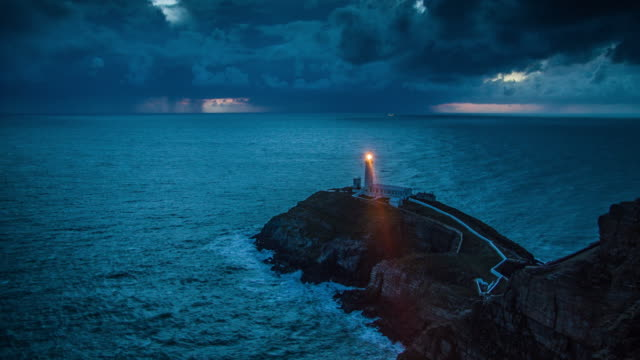 lighthouse with light beam at stormy coastline - lighthouse stock videos & royalty-free footage