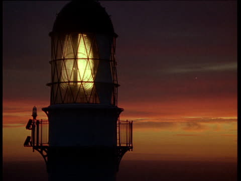 vídeos de stock, filmes e b-roll de lighthouse with turning lamp and light beam at sunset, stephen's island, new zealand - farol estrutura construída