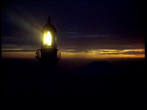 Lighthouse with turning lamp and light beam at sunset, Stephen's Island, New Zealand