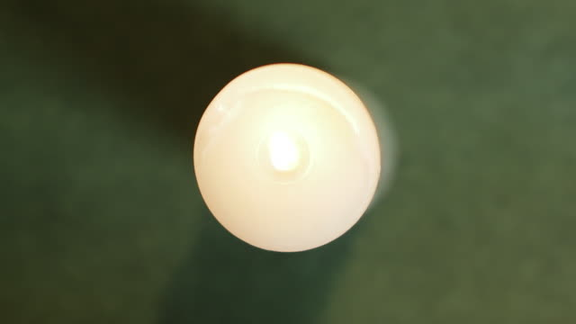 Lighting a white candle with a black gas lighter top view