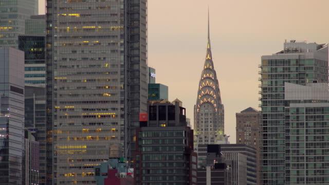 vídeos de stock e filmes b-roll de lighting atop chrysler building in midtown manhattan turn off as a new day begins in new york city. - prédio chrysler