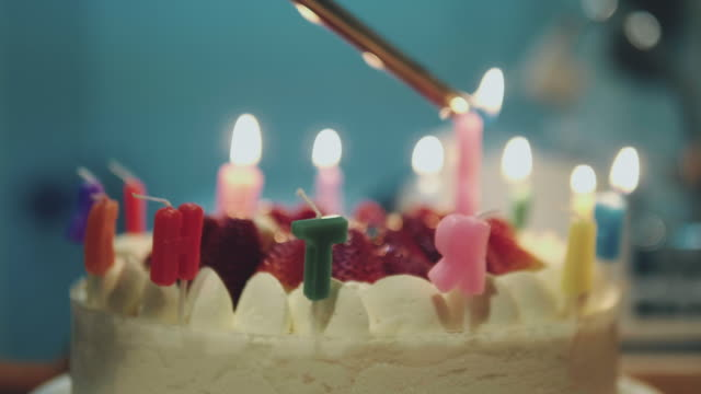 lighting candles on a birthday cake - cards stock videos & royalty-free footage