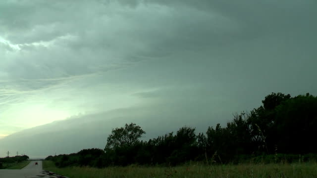 vídeos de stock, filmes e b-roll de lightning bolt shooting out of a supercell thunderstorm - relâmpago em ziguezague