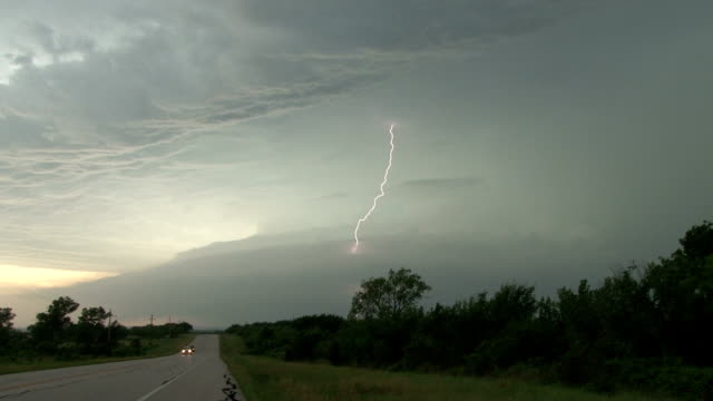vidéos et rushes de lightning bolt shooting out of a supercell thunderstorm - jour