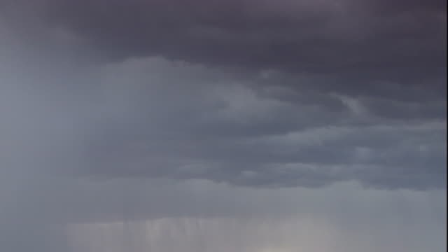 Lightning bolts flash from ominous storm clouds. Available in HD.