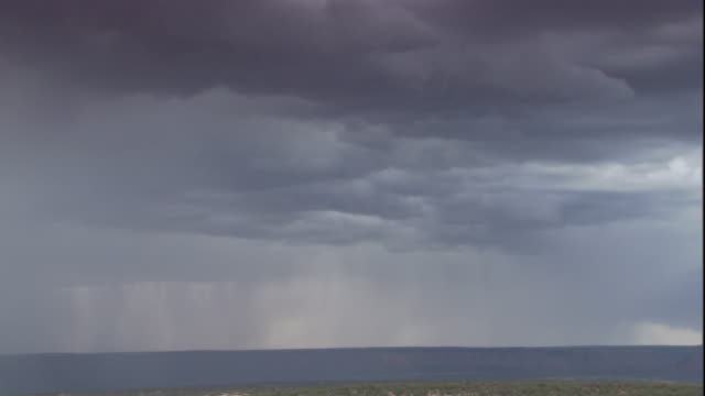 Lightning bolts strike the ocean from ominous storm clouds. Available in HD.