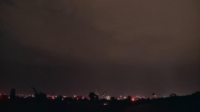 WS T/L Lightning flashes across sky at night over cityscape / Tucson, Arizona, USA