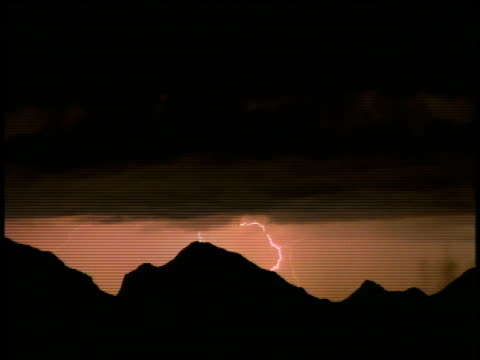 Lightning flashes and strikes from a black, ominous thunderstorm over the mountains.