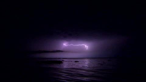 lightning flashes in a dark purple sky. - lightning stock videos & royalty-free footage