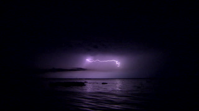 lightning flashes in a dark purple sky. - temporale video stock e b–roll