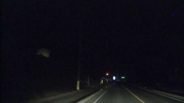 Lightning flashes over a country road as a car travels at night.
