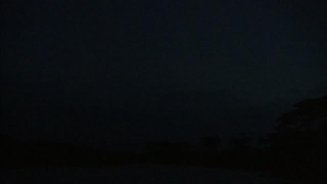 vidéos et rushes de lightning flashes quiver over clouds beyond the shoreline of an african river. - horizon