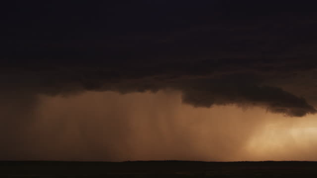 Lightning flashing from an advancing dark cloud as rain dims the sunset glow, time lapse