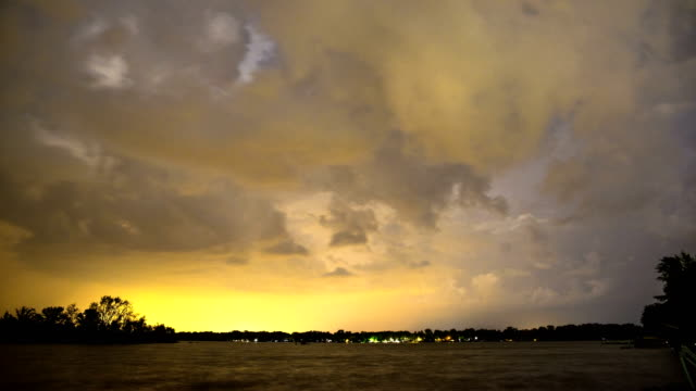 lightning flashing in the clouds as a storm moves over the lake - sciopero video stock e b–roll