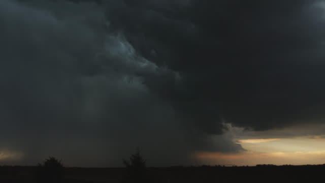 Lightning flickers and a curtain of rain or hail descends at the left  while a dark cloud hovers above sunset glow at the right