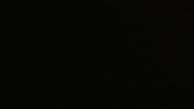 vidéos et rushes de lightning lights up a dark cloudy sky at night. - éclair