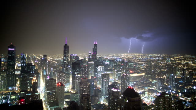 lightning lights up the sky over chicago. - chicago illinois stock-videos und b-roll-filmmaterial