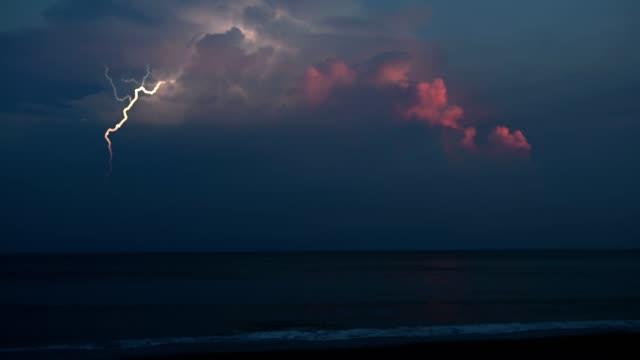 vidéos et rushes de foudre au-dessus de la mer au lever de soleil - éclair