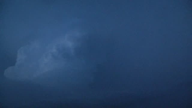 lightning shoots out of a supercell thunderstorm at dusk. - storm cloud stock videos & royalty-free footage