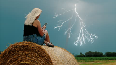 slo mo lightning struck across the sky while woman using her mobile phone - super slow motion stock videos & royalty-free footage