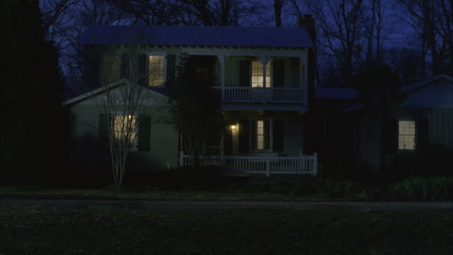 MS Lights are on inside wooden house in rural area at dusk
