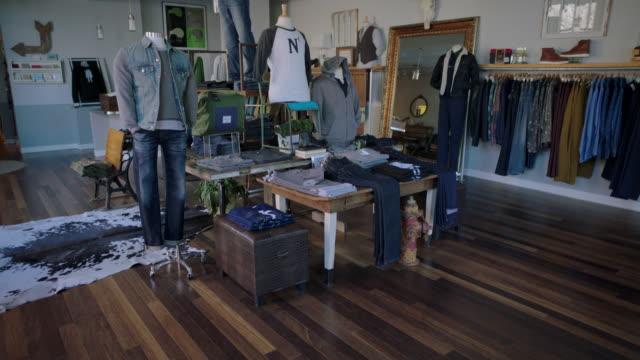 vídeos y material grabado en eventos de stock de lights come on in local clothing retail shop - ropa de caballero