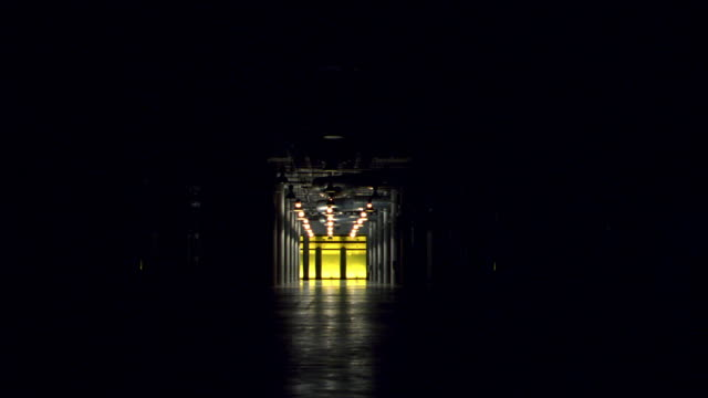 lights come on inside a large, empty industrial building. - corridor stock videos & royalty-free footage
