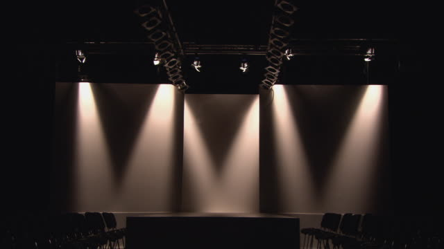 ws lights coming on above fashion show catwalk surrounded by empty chairs/ london, england - grandangolo tecnica fotografica video stock e b–roll
