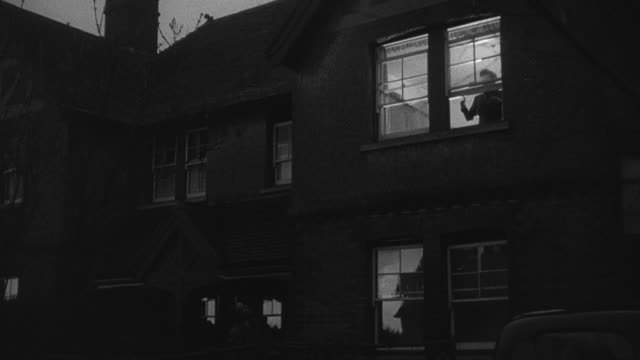 1952 montage lights coming on in second story window of house at twilight, caller on ground talking to resident through upper floor window, and caller riding off through the yard gate and down the lane on bicycle / wadhurst, england, united kingdom - wadhurst stock videos & royalty-free footage