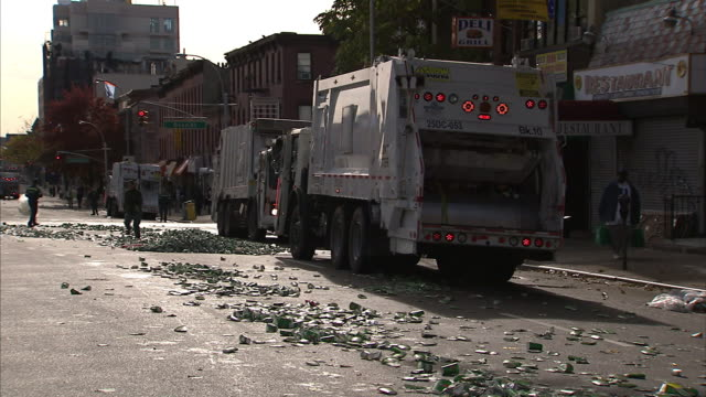 lights flash on a garbage truck while trash collectors clean up a street in new york city. - garbage truck stock videos and b-roll footage