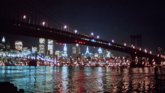 lights from the brooklyn bridge and new york city reflect in the surrounding water. - 1995 stock-videos und b-roll-filmmaterial
