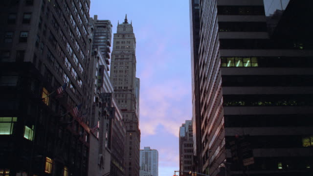 lights glow in the windows of high-rises at golden hour. - golden hour stock videos & royalty-free footage