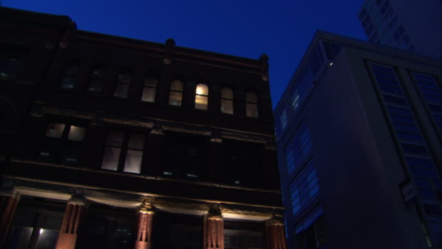 stockvideo's en b-roll-footage met lights glow inside a red brick apartment building situated next to a modern skyscraper. - baksteen