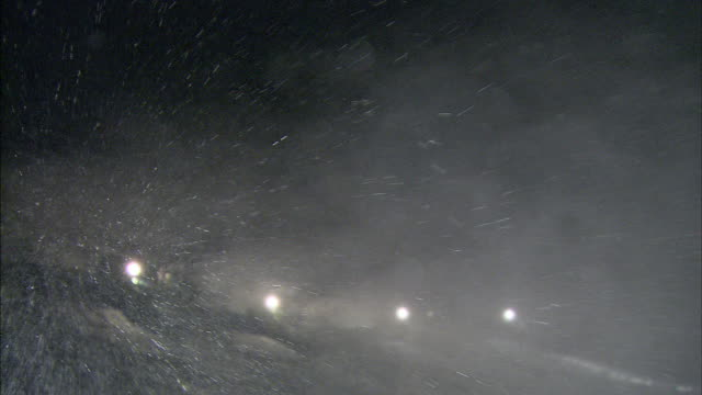 Lights glow through artificial snow drifting in the night air.