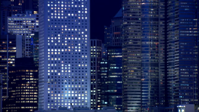 Lights glow through the windows of skyscrapers in Hong Kong. Available in HD.