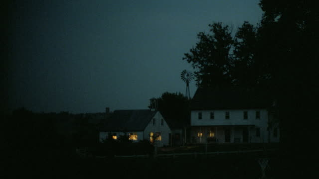 lights glow through the windows of two farmhouses at night. - farmhouse stock videos & royalty-free footage