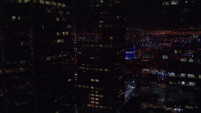 AERIAL Lights glowing in and reflecting off of downtown skyscrapers after dark / Los Angeles, California, United States