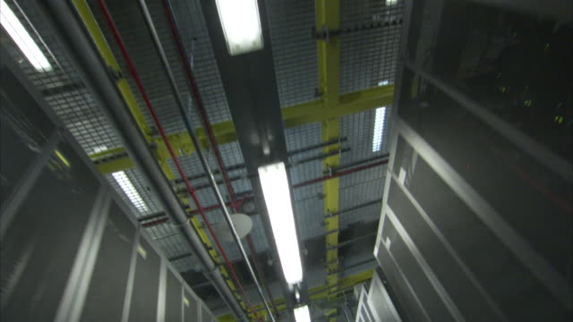 Lights hang above a computer server room.