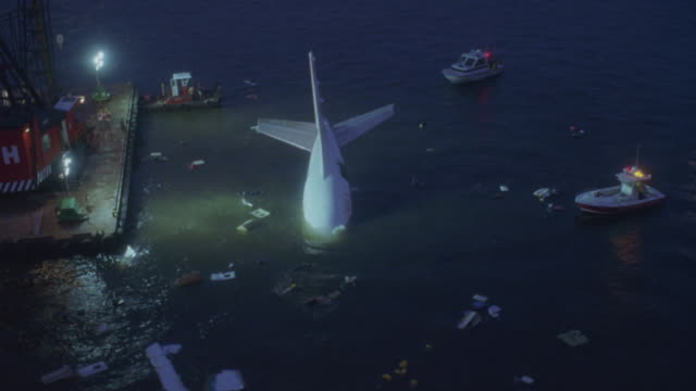 lights illuminate a commercial plane in the water of a bay. - airplane crash stock videos and b-roll footage