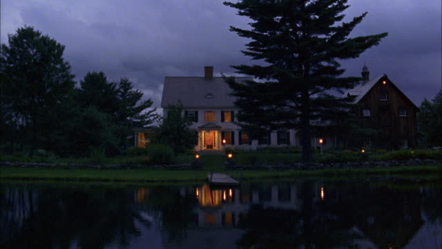 Lights illuminate a country home on a lake.